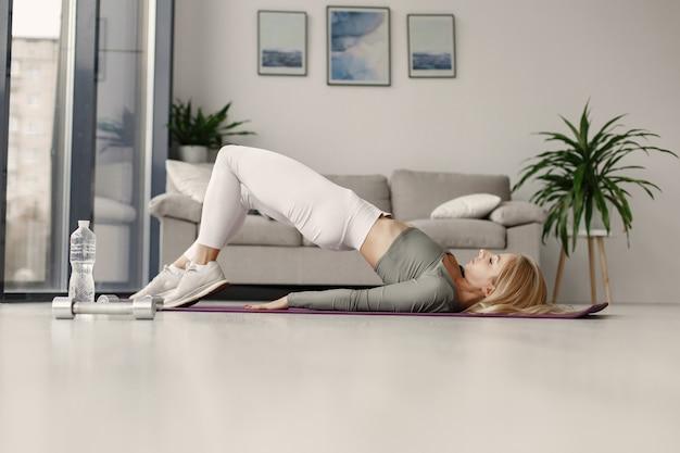 Ragazza a casa. la donna fa yoga. signora con manubri e acqua. Foto Gratuite