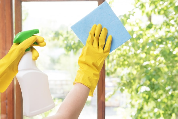 Girl housewife washes the windows in the house in yellow rubber gloves and with a blue rag Premium Photo