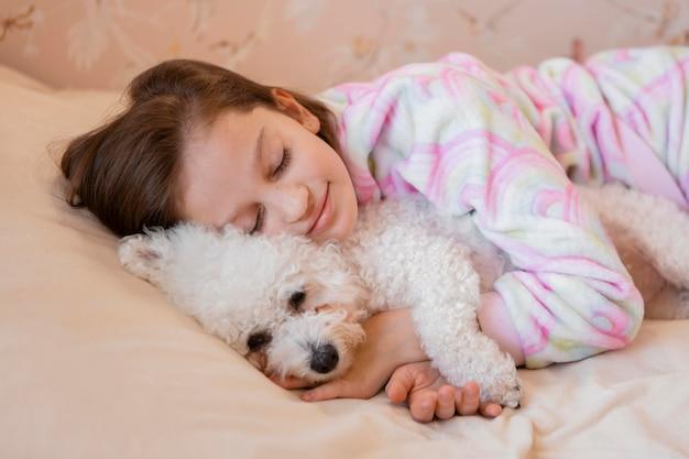 Ragazza che abbraccia il suo cane nel letto mentre dorme Foto Gratuite