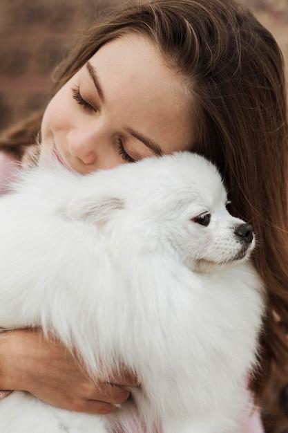 ふわふわの子犬を抱きしめる女の子 無料写真