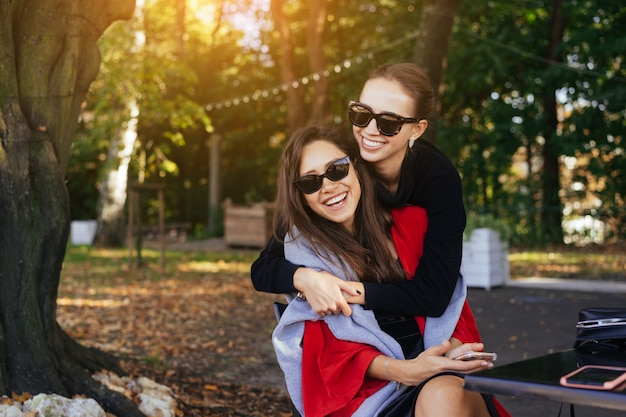 Girl hugging her friend. portrait two girlfriends in the park. Free Photo