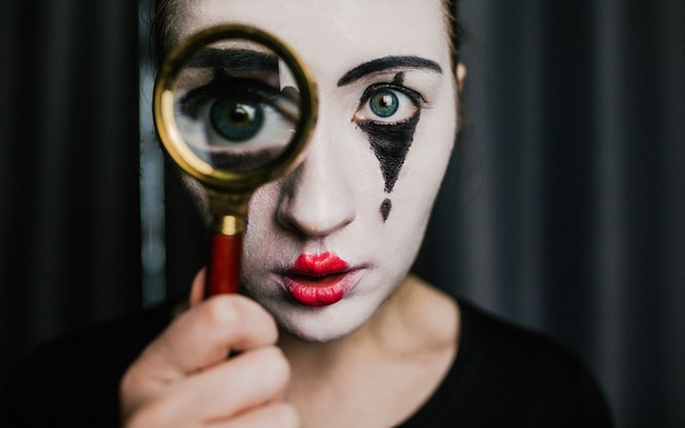 A girl in the image of a mime holds a magnifier. Premium Photo