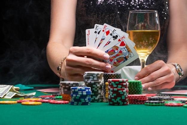 Девушка в казино играет в покер, показывает выигрышные карты | Премиум Фото