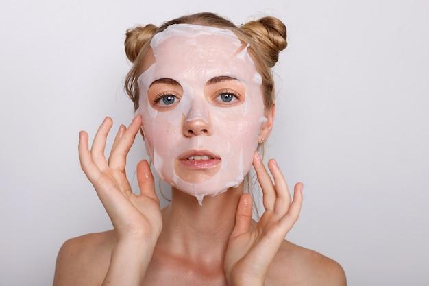 그녀의 얼굴에 헝겊 마스크에 소녀입니다. 미용술 프리미엄 사진