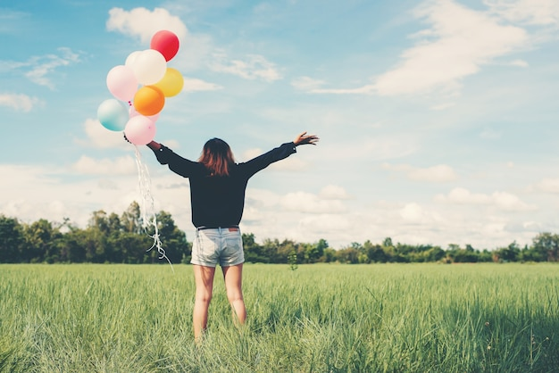 Girl in a field with balloons Free Photo