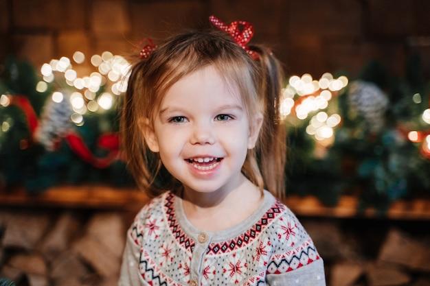 Девушка в сером свитере с хвостиками на фоне новогодней гирлянды Premium Фотографии