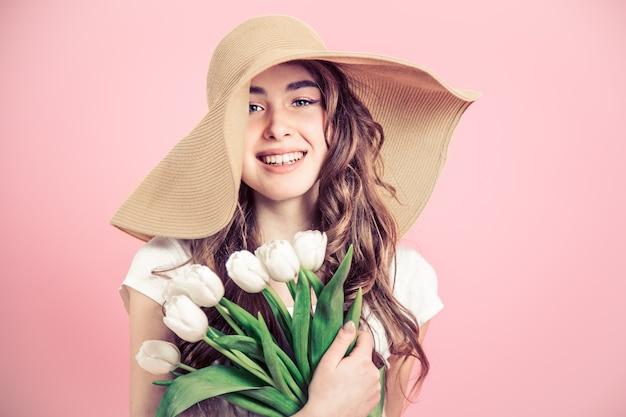 Девушка в шляпе и тюльпаны на цветной стене Бесплатные Фотографии