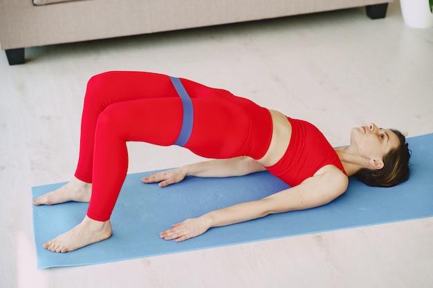 Девушка в красной спортивной форме практикующих йогу дома Бесплатные Фотографии