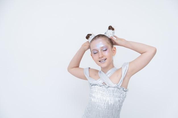 銀のドレスを着た女の子が目を閉じてポニーテールを保持 Premium写真