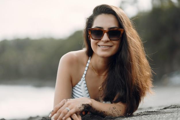 スタイリッシュな水着の女の子がビーチで休憩 無料写真