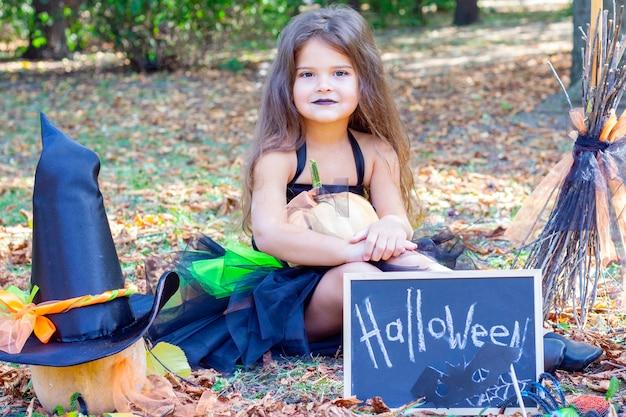Девушка в костюме ведьмы на праздник хеллоуин. плакат с надписью: хэллоуин. девушка сидит на траве Premium Фотографии