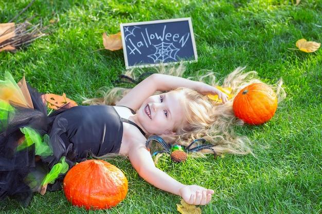 Девушка в костюме ведьмы на праздник хеллоуин. плакат с надписью: хэллоуин. счастливая девушка лежит на траве Premium Фотографии