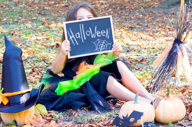 Девушка в костюме ведьмы на праздник хеллоуин. плакат с надписью: хэллоуин. счастливая девушка сидит на траве и закрывает глаза знаком Premium Фотографии