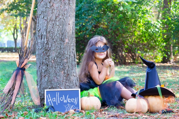 Девушка в костюме ведьмы на праздник хеллоуин. плакат с надписью: хэллоуин. девушка сидит на траве в маске летучей мыши. счастливая девочка Premium Фотографии