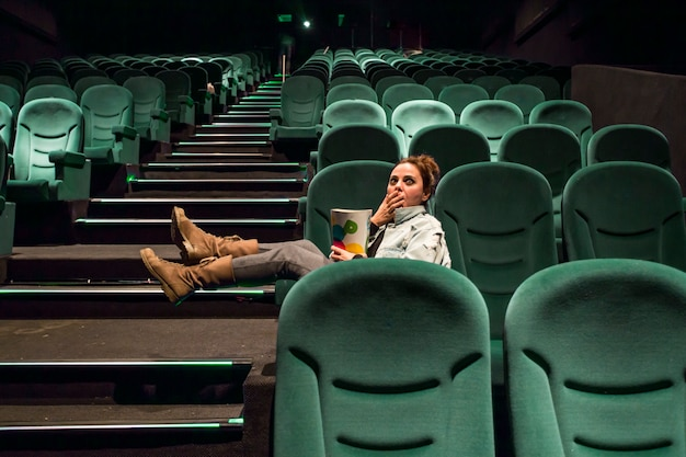Girl in big cinema hall with popcorn Free Photo
