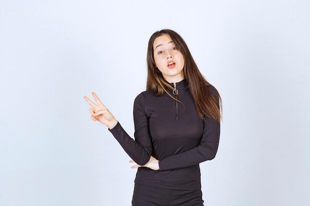 평화와 우정 기호를 보여주는 검은 옷의 소녀. 무료 사진