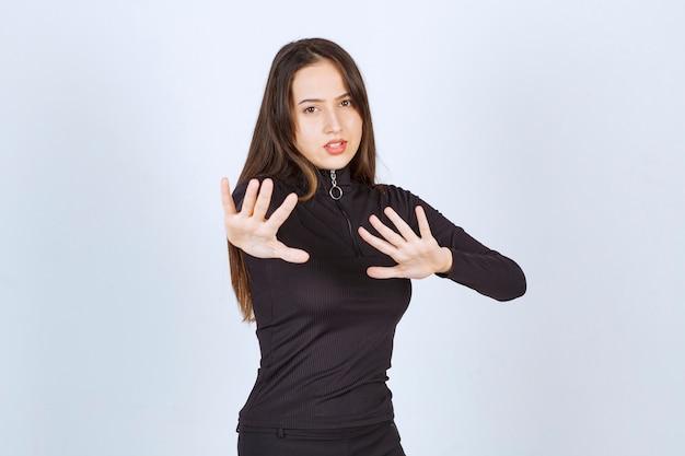 Девушка в черной одежде пытается что-то остановить. Бесплатные Фотографии