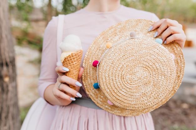 手に飾られたわらの夏の帽子を持って屋外に立っているかわいい紫色のガウンの女の子 無料写真