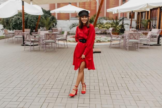 エレガントな赤いベルトのドレスとシティヒールの靴の女の子は、細い脚を示しています。シティカフェでのフルレングスの写真 無料写真