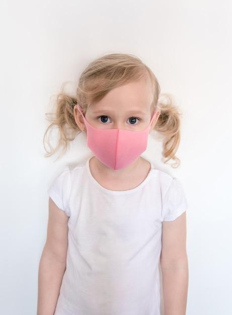 フェイスマスクの女の子。コロナウイルスやインフルエンザの流行時に保護するために、子供はフェイスマスクを着用します。 Premium写真