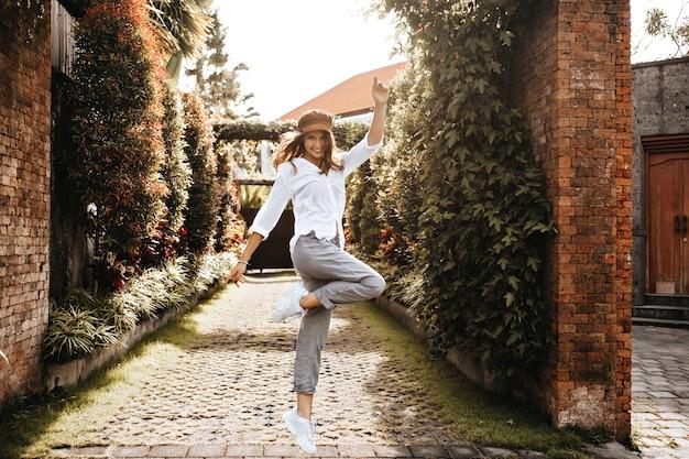 元気いっぱいの女の子が柵にツタを持って古い中庭のスペースにジャンプしています。白い服を着た女性のスナップショット。 無料写真