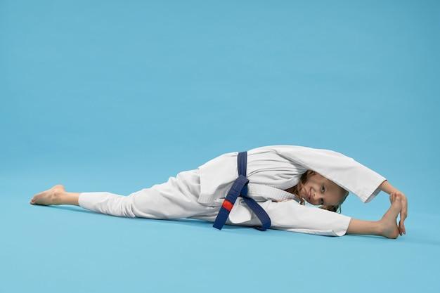 Девушка в кимоно делает шпагат, достигнув ноги. Бесплатные Фотографии