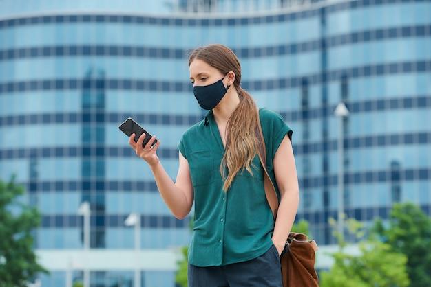 시내에서 바지 주머니에 손을 밀어 스마트 폰 뉴스를 읽는 의료 얼굴 마스크 소녀 프리미엄 사진