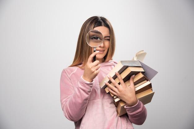 Девушка в розовой рубашке держит стопку книг и пытается прочитать верхнюю с лупой. Бесплатные Фотографии
