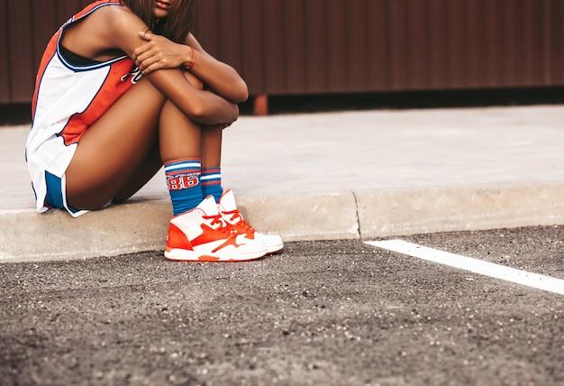 アスファルトの上に座って赤いバスケットボールスポーツ服の女の子 無料写真