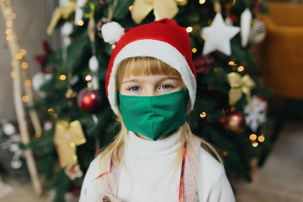 산타의 모자와 마스크, 크리스마스 시간, 휴일, Covid-19, 코로나 바이러스에 걸린 소녀. 프리미엄 사진