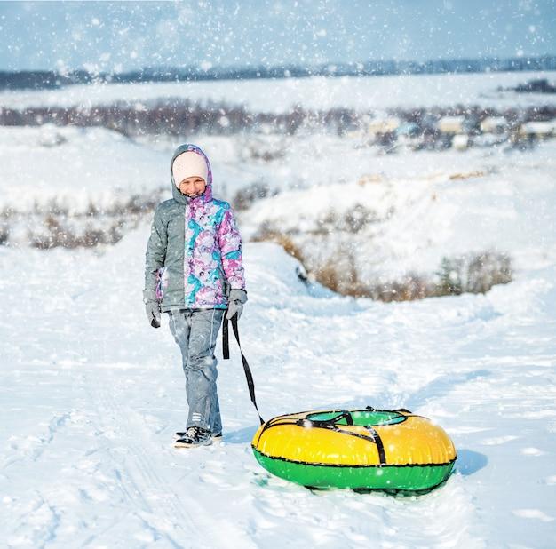 Девушка в лыжной одежде тащит снег на холме Premium Фотографии