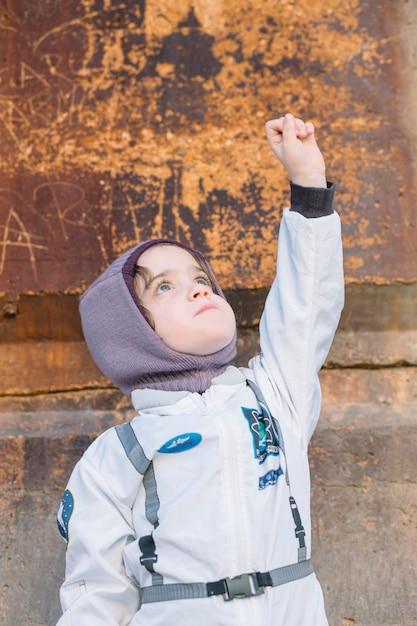 Девушка в скафандре, стоя с рукой вверх Бесплатные Фотографии