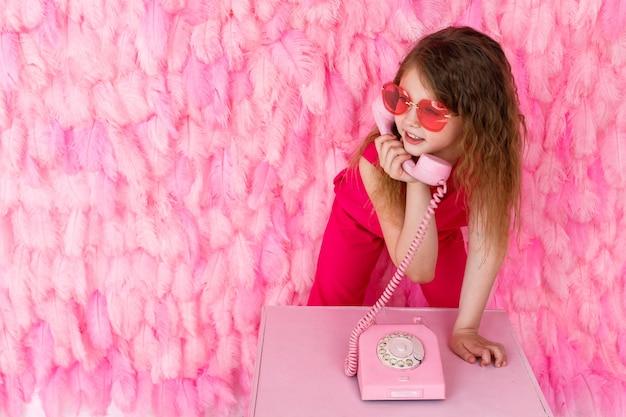 Девушка в стильных розовых очках на розовом разговаривает по розовому телефону Premium Фотографии