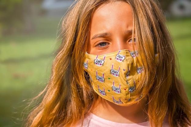 Девушка в маске гуляет в парке в течение дня. Premium Фотографии