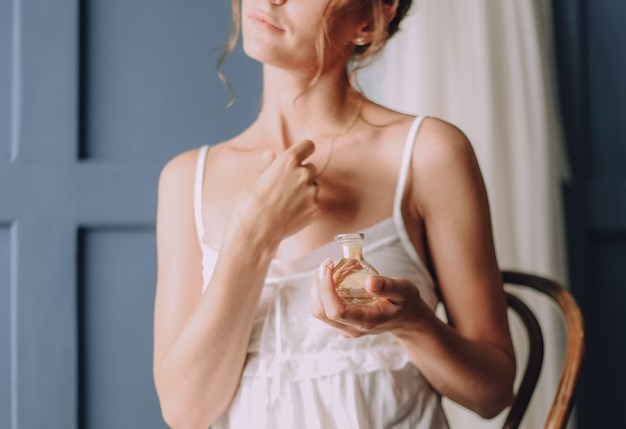 Утром девушка использует духи на шее Бесплатные Фотографии