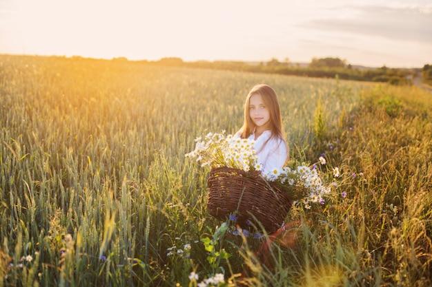 花のバスケットを持つ麦畑の女の子 Premium写真