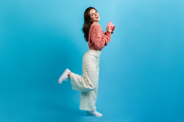 青い壁にピンクのカメラでポーズをとる流行の明るい服装の女の子。魅力的な笑顔の女性がコケティッシュに脚を上げた。 無料写真