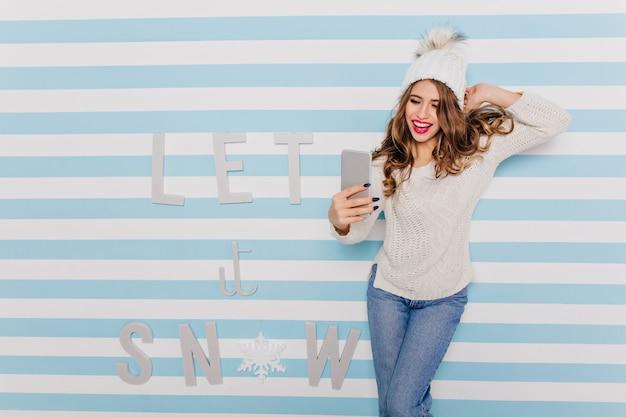 暖かく、冬だがスタイリッシュな服を着た女の子は、電話を反抗的に見て、冬の碑文に対して良い自分撮りのポーズをとる 無料写真