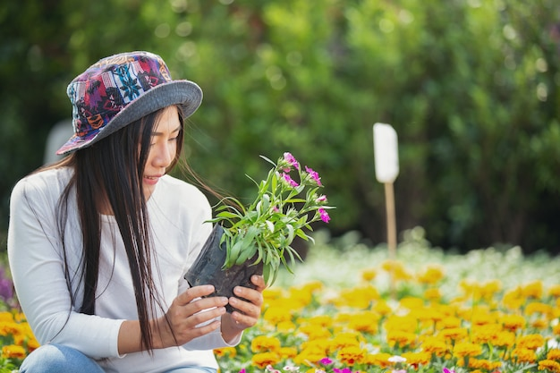 The girl is admiring the flowers in the garden. Free Photo