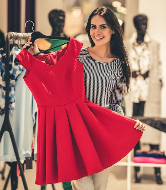 Girl is choosing dress and smiling while doing shopping Premium Photo