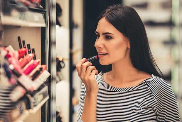 Girl is choosing lipstick while doing shopping in the mall Premium Photo