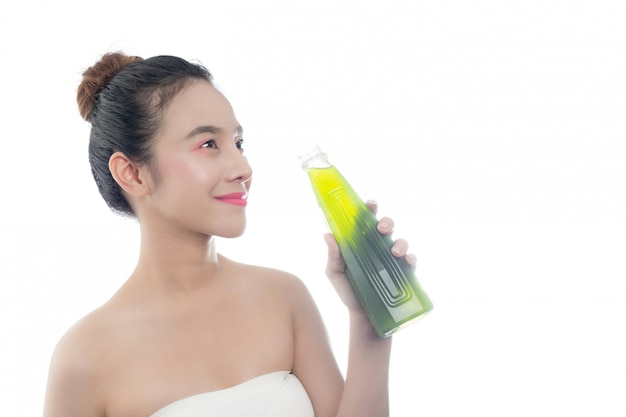 The girl is drinking green water on a white background. Free Photo