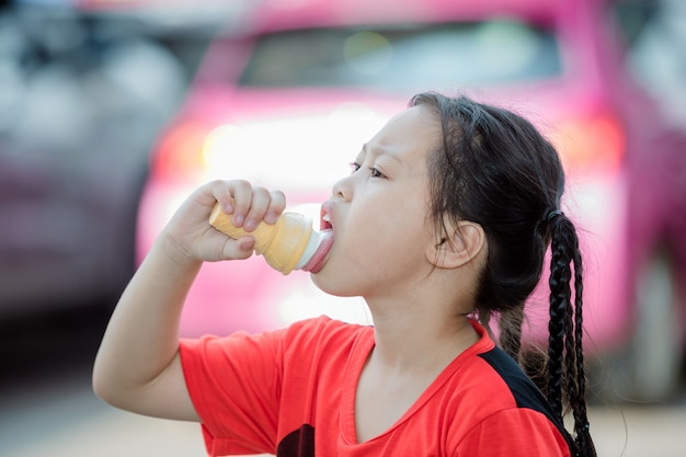 The girl is eating ice cream at the outdoor parking lot. Free Photo