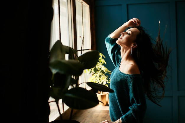 The girl is happy to be in the sun in the morning in her apartment Free Photo