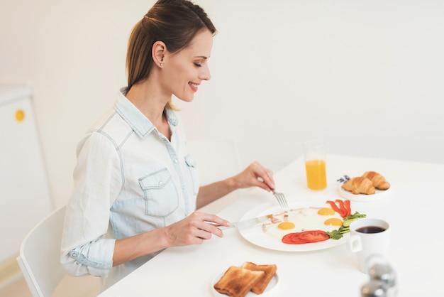 The girl is having breakfast in the kitchen Premium Photo