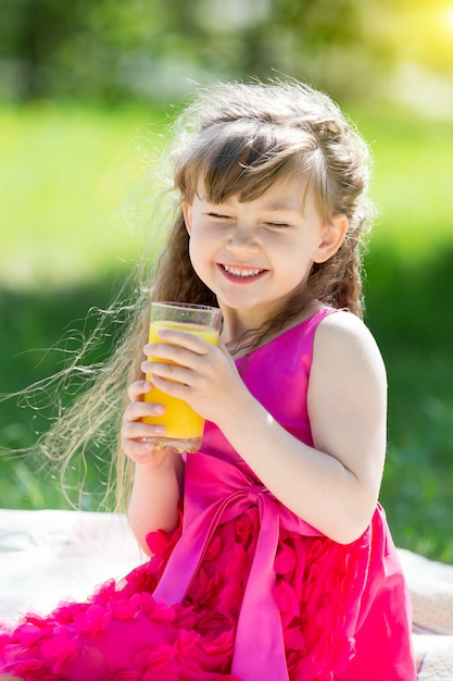 The girl is holding a glass with juice in her hands. Premium Photo