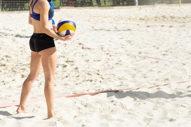 The girl is preparing to serve the ball on the beach volleyball court. Premium Photo