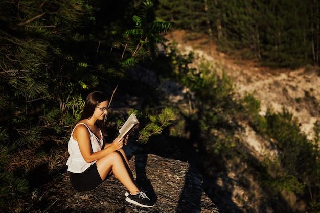 美しい自然の風景に座っている間、女の子は本を読んでいます。 Premium写真