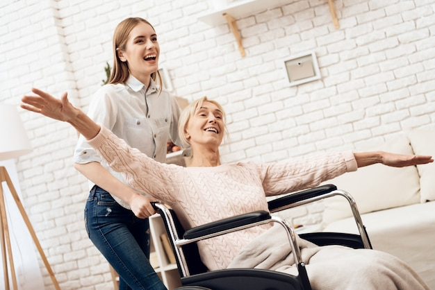 Girl is riding woman in wheelchair. Premium Photo
