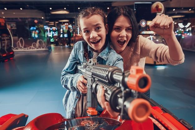 Girl is shooting black gun in arcade Premium Photo